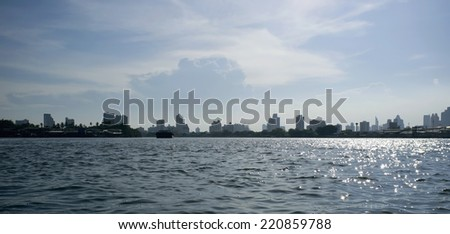Panorama of commercial buildings in Bangkok from the riverside on a sunny day - stock photo