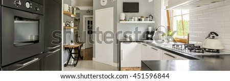 Panorama of contemporary kitchen interior with white cabinets, pantry, built in oven and a large window - stock photo
