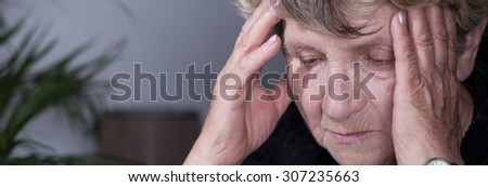 Panorama of despair senior woman having headache