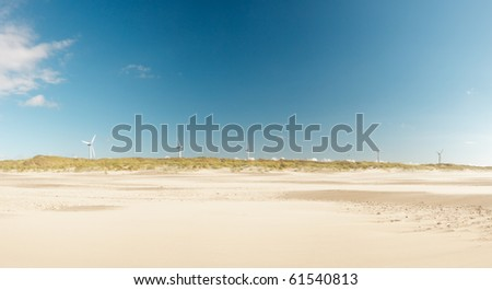 Panorama of dutch beach landscape with dunes and windmills under blue cloudy sky - stock photo