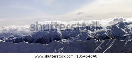 Panorama of evening mountains in clouds. Caucasus Mountains, Georgia, view from ski resort Gudauri. - stock photo