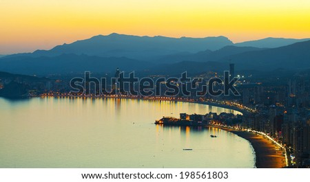 Panorama of evening seaside town with a beach on a background of mountains (Spain, Benidorm)