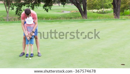 panorama of family at golf field, father teaching his son to play golf