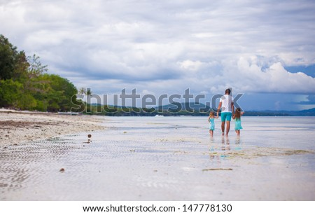 Panorama of father with his young daughters walking along the sea - stock photo