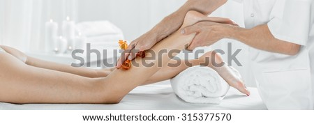 Panorama of female during legs manual lymphatic drainage massage - stock photo