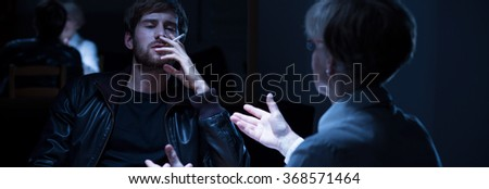 Panorama of female police agent and smoking criminal during interrogation - stock photo