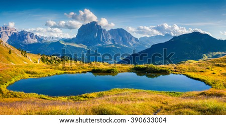 Panorama of Gardena valley with Sassolungo (Langkofel) mountain range. Small lake vnear Troier tourist shelter in Dolomites National Park , South Tyrol. Location Ortisei, S. Cristina and Selva, Italy,