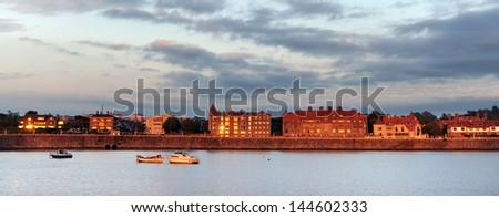 panorama of Getxo promenade at twilight with some boats
