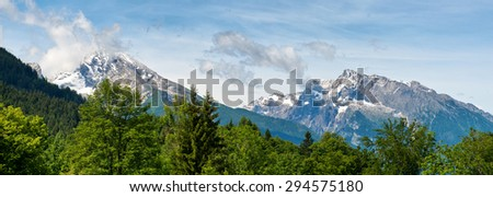 Panorama of green fir trees and snow-capped rocky mountain peaks beneath blue sky and whispy white clouds - stock photo
