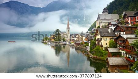Panorama of Hallstatt mountain village. Foggy morning - stock photo