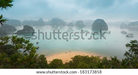 Panorama of Halong Bay in Vietnam with green leaves and beach in foreground. Cliffs and rocks standing out of water with boats floating around. Light fog in distance. Popular travel destination. - stock photo