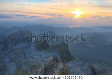 panorama of high alpine ragged sharp karst mountain top ranges disappear in misty distance and green meadow at sunset, Switzerland - stock photo