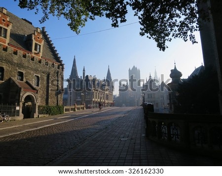 Panorama of historical center of Gent with medieval house facades, St Michael's Bridge, West Flanders in Belgium.  Old town in the morning, slight fog, trees and Cathedral, old towers.             - stock photo