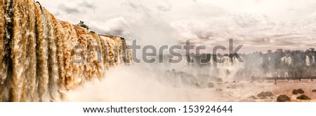Panorama of Iguazu falls in Foz do Iguacu, Brazil. Warm storm in the sky and brown water due to rains season. - stock photo