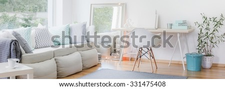 Panorama of interior with large sofa and simple study area - stock photo