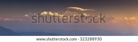 Panorama of Kanchenjunga range peak in early morning light with thick mist Darjeeling, Sikkim, India - stock photo