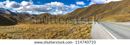 Panorama of Lindis  Pass, South Island, New Zealand showing a road hedding off around a bend and into the distance with snow capped mountains, brown tussock grass and white clouds on a blue sky