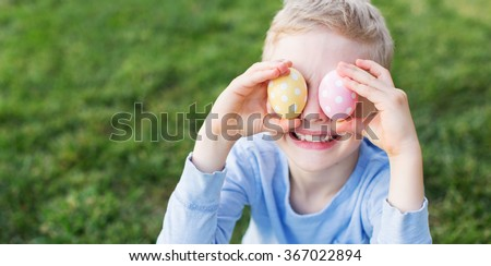 panorama of little boy being silly and having fun at spring time covering his eyes with colorful eggs