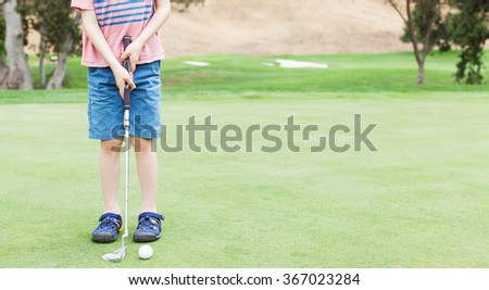 panorama of little boy learning to play golf