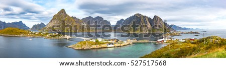Panorama of Lofoten scenery from top of Mt. Olenilsoy near Hamnoy and Reine in a sunny day, partly cloudy sky and good weather. Beautiful cloud and mountain background with small island and bridge.