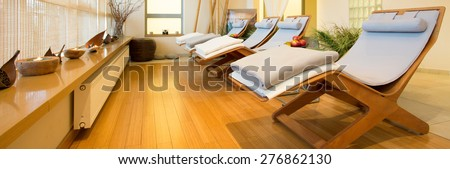 Panorama of loungers in cozy spa room - stock photo