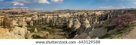 Panorama of Love Valley in Cappadocia in spring - romantic travel in Turkey. Cappadocia landmarks with fairy chimneys and scenic hills between the volcanic mountains of Erciyes, Melendiz and Hassan.