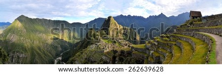 Panorama of Machu Picchu terraces, watcher's hut and Wuayna Picchu with shadow in early morning light. Machu Picchu is the famous lost city of the Incas near the river Urubamba located in the region - stock photo