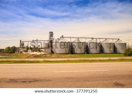 panorama of metal tanks of modern silo in countryside with road on foreground - stock photo