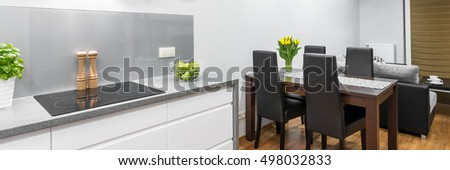 Panorama of modern kitchen in white and grey with dark wooden family dining set