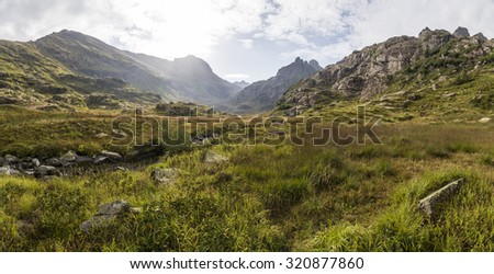 panorama of mountain scenery with meadow, located in a river valley in Abkhazia, Caucasus Mountains - stock photo