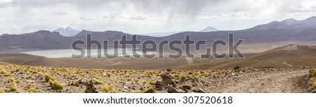 Panorama of mountains and white salt pan in Eduardo Avaroa Andean Fauna National Reserve against a clear blue sky, Bolivia - stock photo