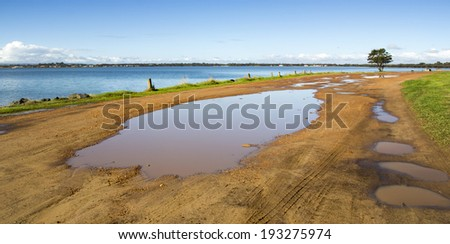 Panorama of  muddy puddle  near  the calm waters of the Leschenault Estuary  near Australind Western Australia after a shower of rain  on an early morning in late autumn. - stock photo