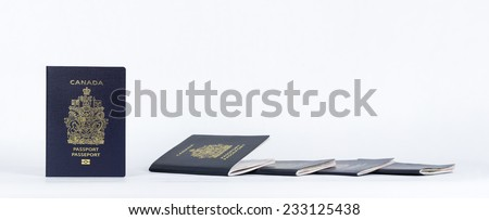 Panorama of new and old Canadian Passports on white background with slight reflection. - stock photo