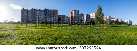 Panorama of new district on  background of green grass and bright blue sky