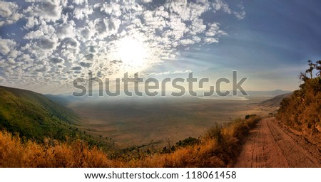 Panorama of Ngorongoro Crater with sunny blue sky with few clounds and gravel road. - stock photo