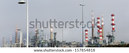 Panorama of part of a big oil refinery and powerplant near a road - stock photo