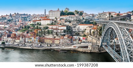Panorama of Porto with buildings on hill and the Luis bridge built by Eiffel - stock photo