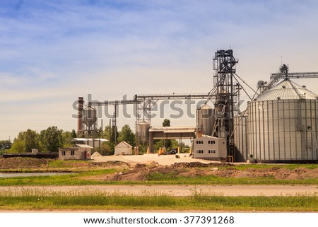 panorama of production yard and metal tank of modern silo in countryside - stock photo