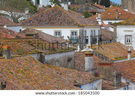 Panorama of red tiled roofs in beautiful medieval village in Obidos, Portugal - stock photo
