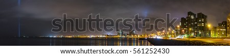 Panorama of Reykjavik Iceland at night shows the bay with bright spotlights and city architecture lining the water.