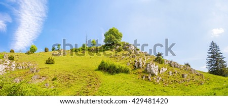 Panorama of rocks at valley Eselsburger Tal near river Brenz - jewel of the swabian alps, meadow in front - stock photo