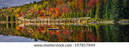 Panorama of scenic route through fall forest with colorful autumn foliage reflecting in lake. Highway 60, Algonquin Park, Ontario, Canada. - stock photo