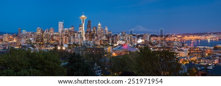 Panorama of Seattle downtown skyline and Mt. Rainier at night, Washington. - stock photo