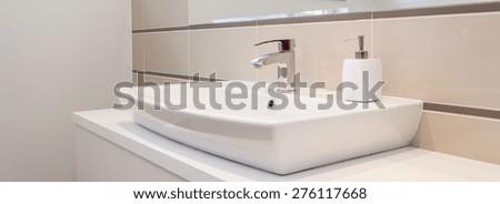Panorama of silver tap in white elegant bathroom - stock photo