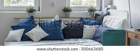 Panorama of single bed with decorative cushions in light interior - stock photo