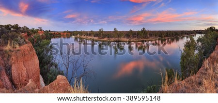 Panorama of still river water of Murray between elevated Victoria Red Cliffs and low NSW plains at sunset