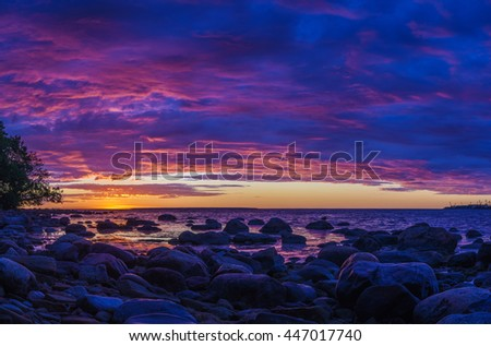 Panorama of stony coast of Baltic sea by vivid sunset with fiery cloudscape - stock photo