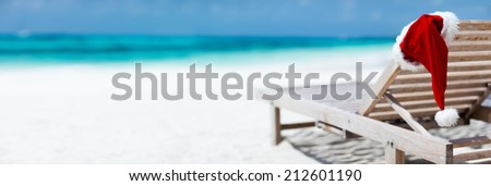 Panorama of sun chair with Santa hats on beautiful tropical beach with white sand and turquoise water, perfect Christmas vacation - stock photo