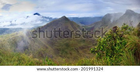 Panorama of The Batur volcano crater in cloudy weather with Agung volcano in behind, Bali, Indonesia