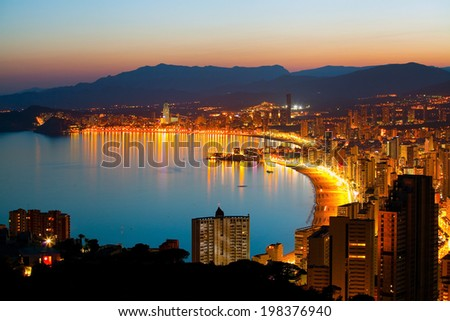 Panorama of the beach in Benidorm and night lights of the city at sunset (Spanish coast)